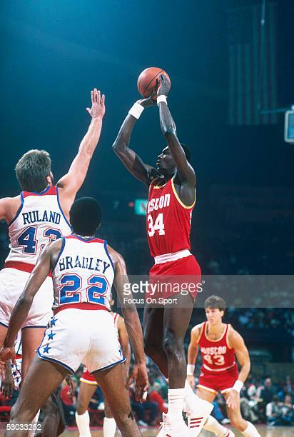 Center Hakeem Olajuwon of the Houston Rockets takes a jumpshot over the Washington Bullets defence during a game at Capital Centre circa 1984 in...