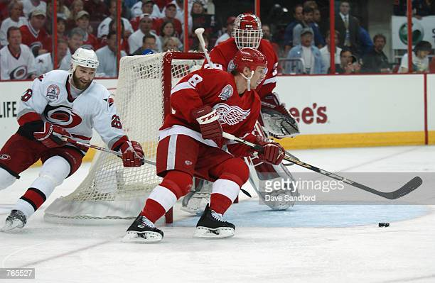Center Igor Larionov of the Detroit Red Wings skates arouns his own net chased by left wing Erik Cole of the Carolina Hurricanes during game three of...