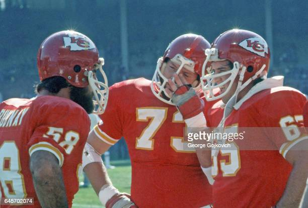 Center Jack Rudnay of the Kansas City Chiefs talks to offensive linemen Bob Simmons and Tom Condon during a game against the Cleveland Browns at...