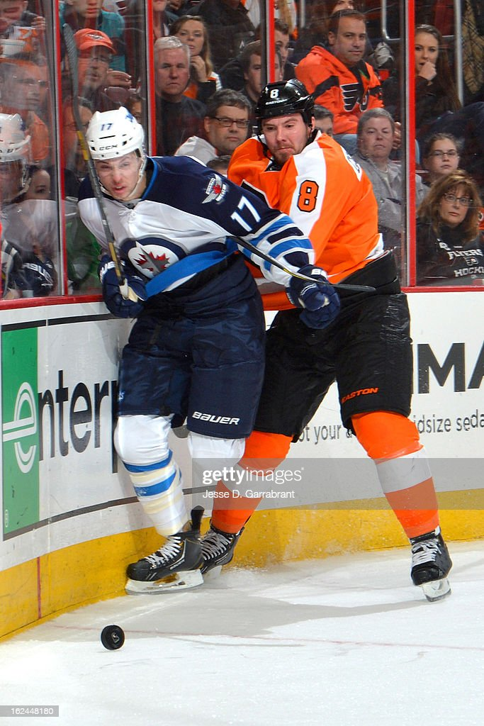 Center James Wright #17 of the Winnipeg Jets is checked against the boards by Nicklas Grossmann #8 of the Philadelphia Flyers on February 23, 2013 at the Wells Fargo Center in Philadelphia, Pennsylvania.