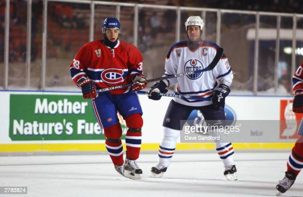 Center Jan Bulis of the Montreal Canadiens stands next to defenseman Jason Smith of the Edmonton Oilers at the Molson Canadien Heritage Classic on...