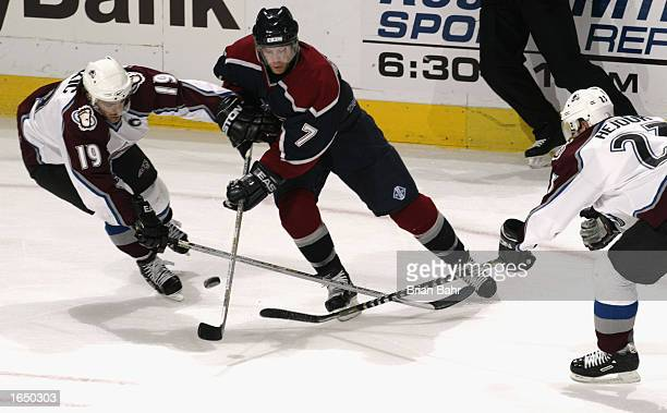 Center Joe Sakic of the Colorado Avalanche fights for control of the puck against center Brendan Morrison of the Vancouver Canucks in the first...