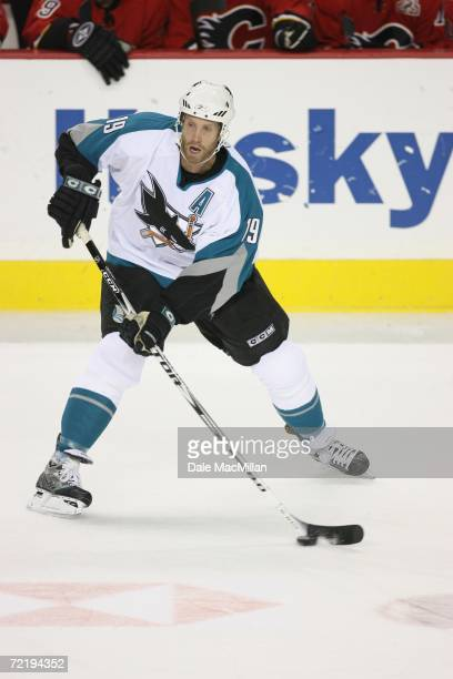 Center Joe Thornton of the San Jose Sharks plays the puck against the Calgary Flames during the NHL game at Pengrowth Saddledome on October 9 2006 in...