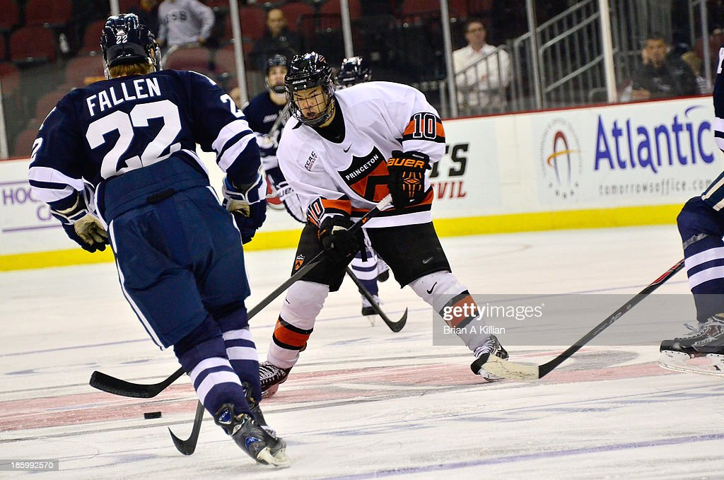 Center Jonathan Liau #10 of the Princeton Tigers tries to skate past defenseman Tommy Fallen #22 of the Yale Bulldogs at Prudential Center on October 26, 2013 in Newark, New Jersey. The Yale Bulldogs defeated the Princeton Tigers, 3-2.