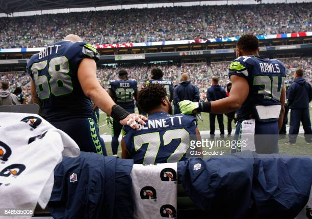 Center Justin Britt of the Seattle Seahawks left and running back Thomas Rawls right join defensive end Michael Bennett on the bench during the...