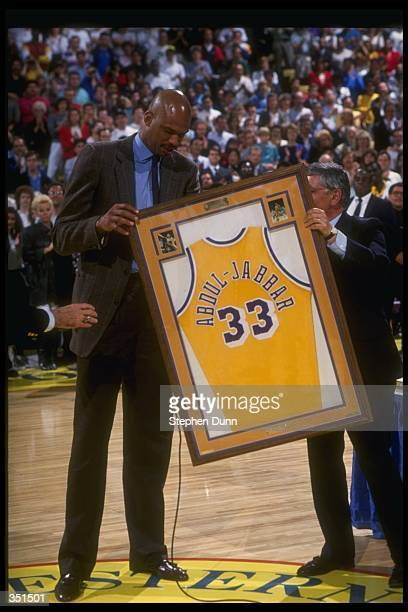 Center Kareem AbdulJabbar of the Los Angeles Lakers poses with his framed jersey at its retirement ceremony Mandatory Credit Stephen Dunn /Allsport...