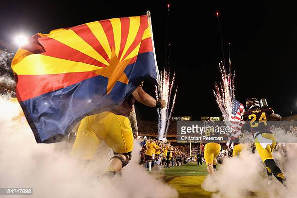 Center Kody Koebensky defensive tackle Jake Sheffield and cornerback Osahon Irabor of the Arizona State Sun Devils lead teammates out onto the field...