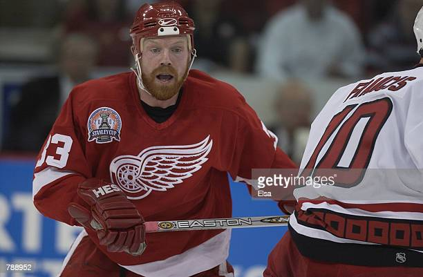 Center Kris Draper of the Detroit Red Wings eyes the play against center Ron Francis of the Carolina Hurricanes during game three of the NHL Stanley...