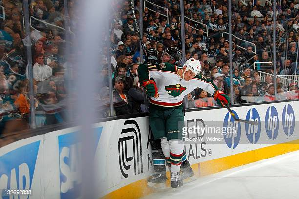 Center Kyle Brodziak the Minnesota Wild collides with defenseman Colin White of the San Jose Sharks at the HP Pavilion on November 10 2011 in San...
