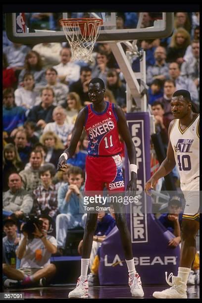 Center Manute Bol of the Philadelphia 76ers looks on during a game against the Utah Jazz at the Delta Center in Salt Lake City, Utah.