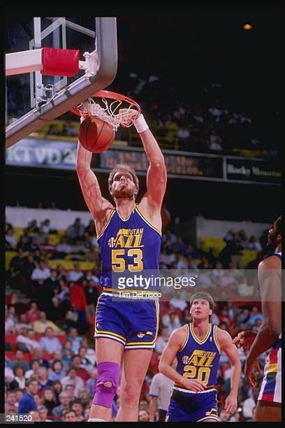 Center Mark Eaton of the Utah Jazz slam dunks as teammate guard Bobby Hansen looks on during a game against the Denver Nuggets at McNichols Arena in...