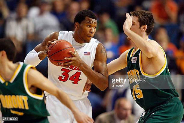Center Marreese Speights of the Florida Gators looks to move the ball against forward Garrett Kissel of the Vermont Catamounts during the game on...