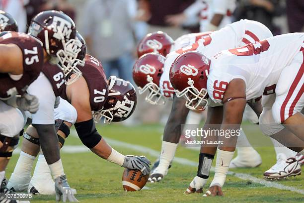 Center Matt Allen prepares to snap the ball while Offensive linemen Patrick Lewis and Jake Matthews of the Texas AM Aggies get ready to block...