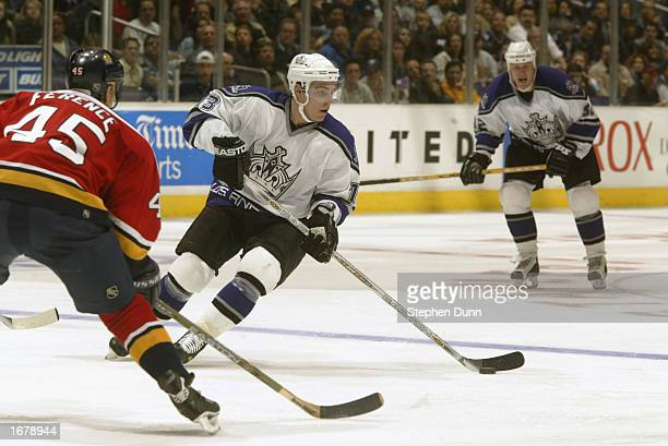 Center Michael Cammalleri of the Los Angeles Kings skates with the puck while being defended by Brad Ference of the Florida Panthers during the NHL...