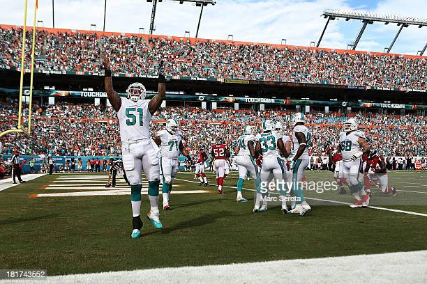 Center Mike Pouncey of the Miami Dolphins celebrates a touchdown by teammate Daniel Thomas against the Atlanta Falcons at Sun Life Stadium on...