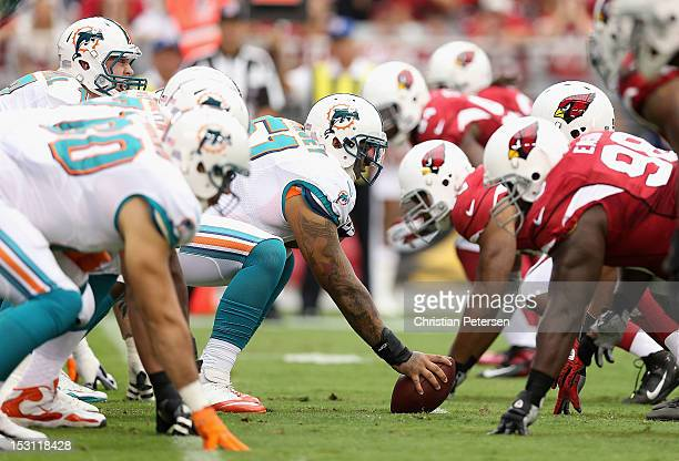Center Mike Pouncey of the Miami Dolphins prepares to snap the football to quarterback Ryan Tannehill during the NFL game against the Arizona...
