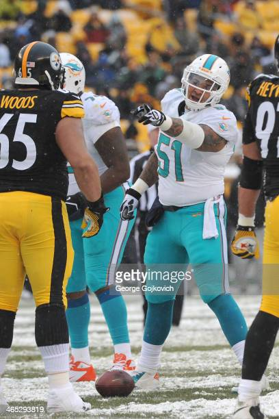 Center Mike Pouncey of the Miami Dolphins signals at the line of scrimmage as defensive lineman Al Woods of the Pittsburgh Steelers looks on during a...