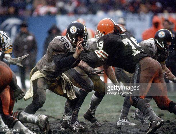 Center Mike Webster of the Pittsburgh Steelers blocks against defensive lineman Bob Golic of the Cleveland Browns in the rain and mud during a game...