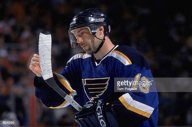 Center Ray Ferraro of the St Louis Blues examines his hockey stick during the NHL game against the Detroit Red Wings at the Joe Louis Arena in...