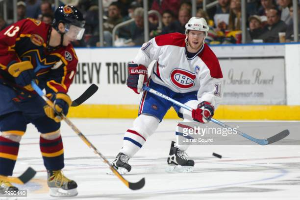 Center Saku Koivu of the Montreal Canadiens chases the puck during the game against the Atlanta Thrashers at Philips Arena on January 14 2004 in...