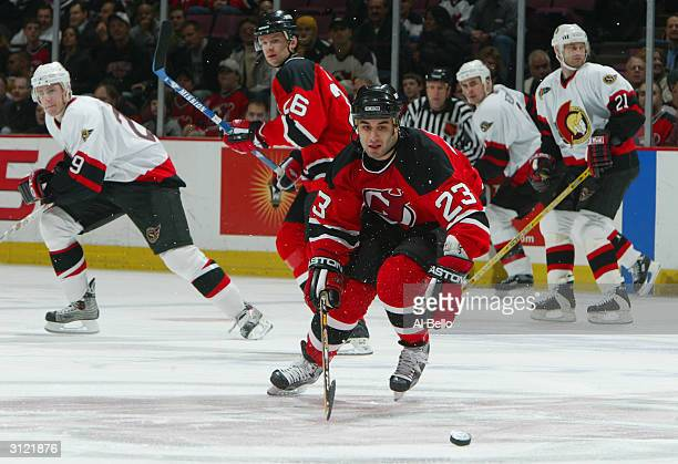 Center Scott Gomez of the New Jersey Devils advances the puck against the Ottawa Senators during the game at the Continental Airlines Arena on...