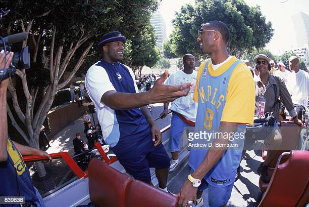 Center Shaquille O'Neal of the Los Angeles Lakers celebrates with teammate Kobe Bryant on the parade route honoring their third consecutive NBA...