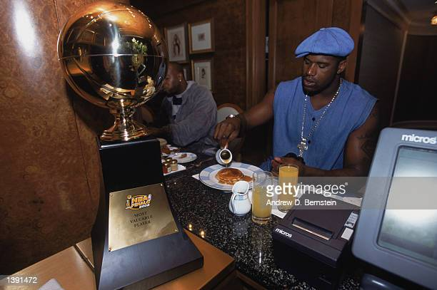 Center Shaquille O'Neal of the Los Angeles Lakers eats his breakfast with his Series MVP trophy at hand the day after winning Game Four of the 2002...