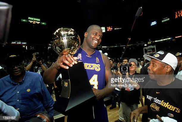 Center Shaquille O'Neal of the Los Angeles Lakers holds up his Finals Series MVP trophy as his grandfather looks on proudly after winning Game Four...