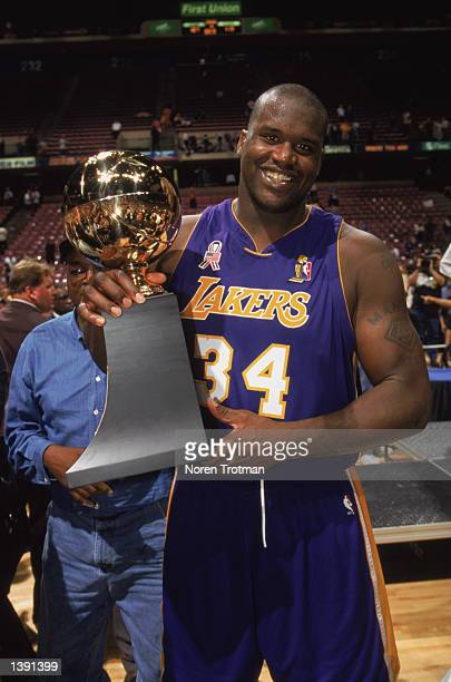 Center Shaquille O'Neal of the Los Angeles Lakers holds up his Series MVP trophy after Game Four of the 2002 NBA Finals against the New Jersey Nets...