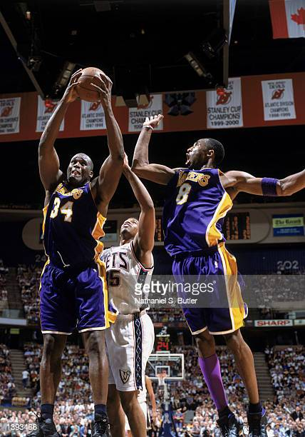 Center Shaquille O'Neal of the Los Angeles Lakers rebounds over teammate Kobe Bryant and center Jason Collins of the New Jersey Nets during Game Four...