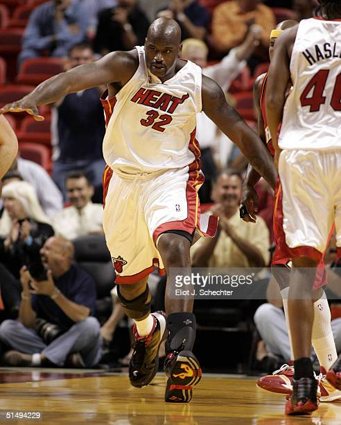Center Shaquille O'Neal of the Miami Heat runs down the court after scoring against the Atlanta Hawks in NBA preseason action October 18, 2004 at the...