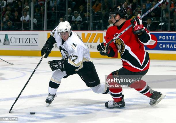Center Sidney Crosby of the Pittsburgh Penguins moves the puck against defenseman Christoph Schubert of the Ottawa Senators during a preseason game...