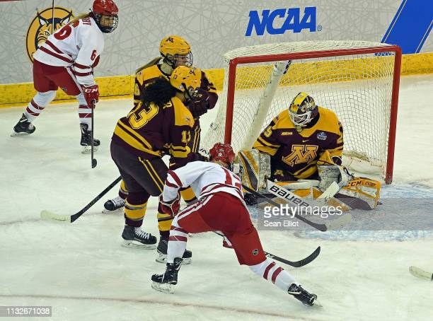 Center Sophia Shaver of the Wisconsin Badgers pushes the puck past goalie Alex Gulstene of the Minnesota Golden Gophers for the opening goal of the...