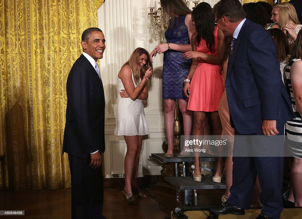 Center Stefanie Dolson (2nd L) of the University of Connecticut women's basketball team shares a laugh with U.S. President Barack Obama (L) after she slipped off the riser during an East Room event at the White House June 9, 2014 in Washington, DC. President Obama hosted the NCAA Champion UConn Huskies Men's and Women's Basketball teams to honor the teams and their 2014 NCAA Championships.