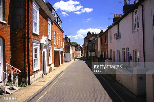 center view of an old english street on a partly cloudy day - winchester hampshire stock photos and pictures