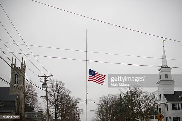 Centered between 2 churches on Main Street in Newtown CT the American flag flies at half mast on Sunday December 16 2 days following a mass shooting...