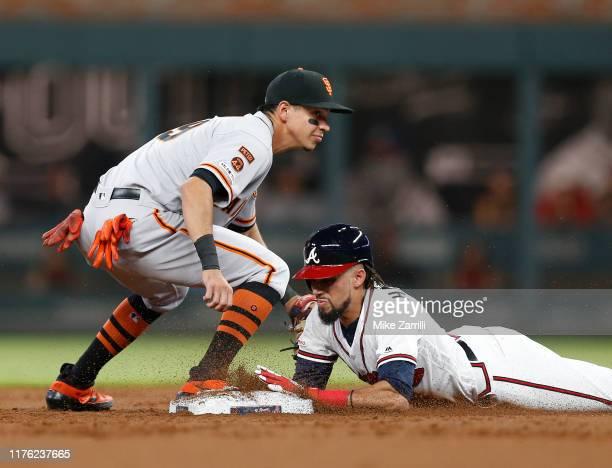 Centerfielder Billy Hamilton of the Atlanta Braves slides into second base under the tag of shortstop Mauricio Dubon of the San Francisco Giants...