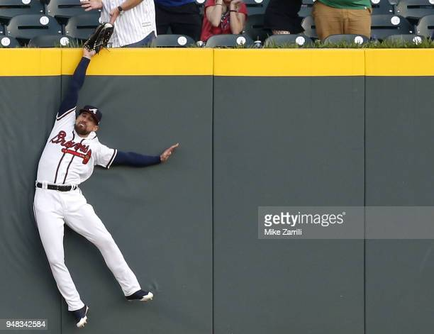 Centerfielder Ender Inciarte of the Atlanta Braves catches a ball over the outfield wall to rob a home run from Philadelphia Phillies left fielder...