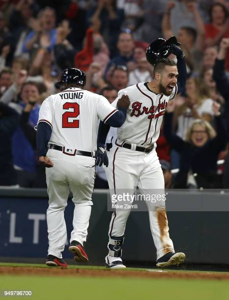 Centerfielder Ender Inciarte of the Atlanta Braves is congratulated by first base coach Eric Young Sr after laying down a game winning squeeze bunt...