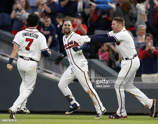 Centerfielder Ender Inciarte of the Atlanta Braves is congratulated by first baseman Freddie Freeman and shortstop Dansby Swanson of the Atlanta...