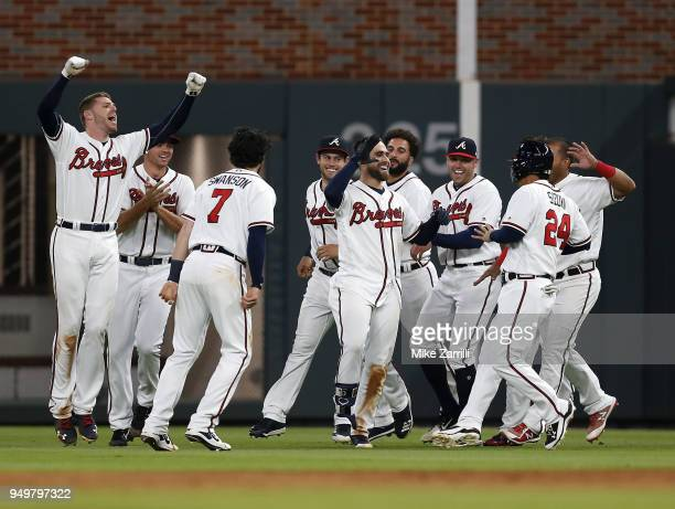 Centerfielder Ender Inciarte of the Atlanta Braves is congratulated by teammates after Inciarte's game winning squeeze bunt during the game against...
