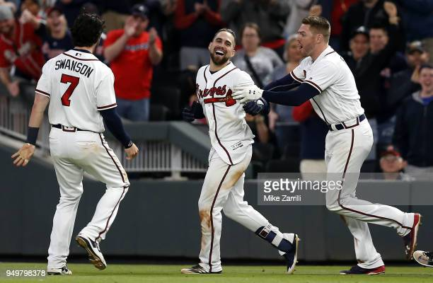 Centerfielder Ender Inciarte of the Atlanta Braves is congratulated by first baseman Freddie Freeman and shortstop Dansby Swanson after Inciarte's...