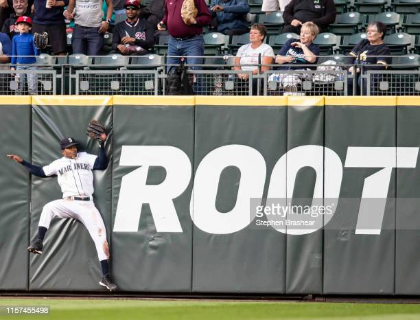 Centerfielder Mallex Smith of the Seattle Mariners hits the wall after catching a fly ball hit by Logan Forsythe of the Texas Rangers during the...