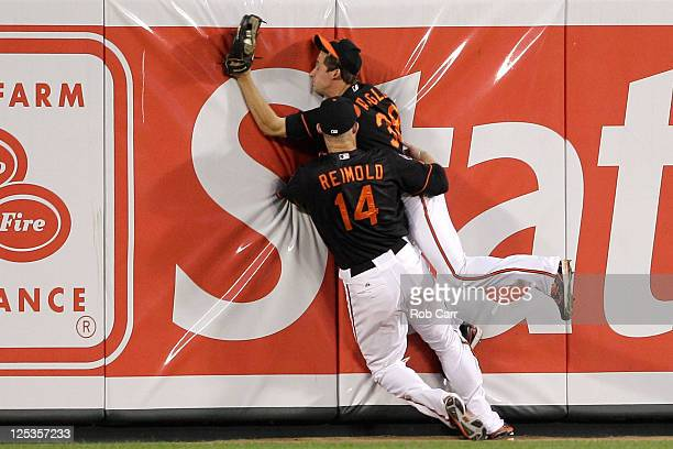 Centerfielder Matt Angle of the Baltimore Orioles collides with right fielder Nolan Reimold after catching a ball for an out hit by Howard Kendrick...