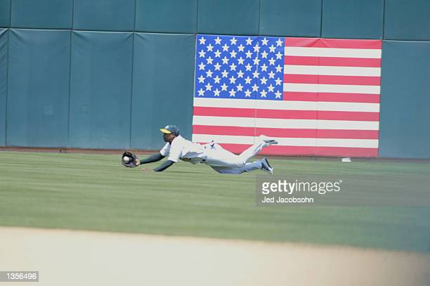 Centerfielder Terrence Long of the Oakland A's dives and catches a ball hit by catcher Tom Wilson of the Toronto Blue Jays at the Network Associates...