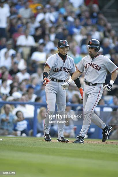 Centerfielder Tsuyoshi Shinjo of the San Francisco Giant greets shortstop Rich Aurilia at home plate during the game against the Los Angeles Dodgers...