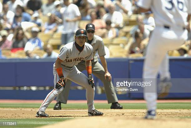 Centerfielder Tsuyoshi Shinjo of the San Francisco Giants eyes the pitcher as he leads off first base against the Los Angeles Dodgers during the MLB...