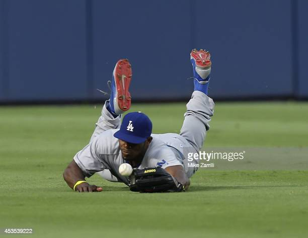 Centerfielder Yasiel Puig of the Los Angeles Dodgers dives unsuccessfully to catch a fly ball during the third inning of the game against the Atlanta...