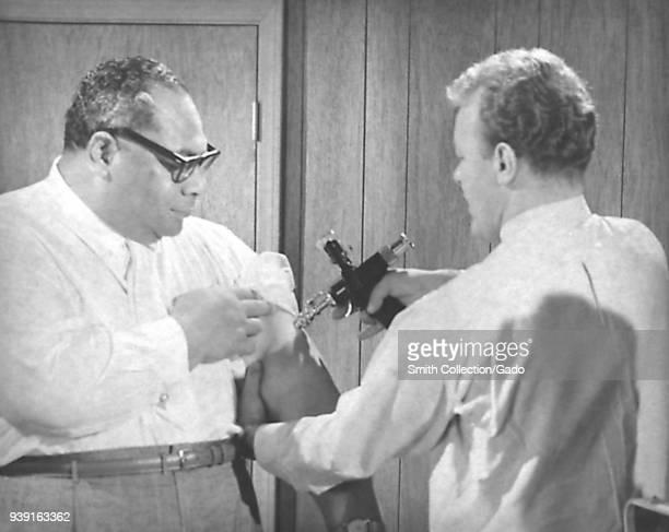 Centers for Disease Control administrator Ron Roberto, MD vaccinating Prince Taufa'ahau Tupou IV of Tonga, 1969. Image courtesy Centers for Disease...