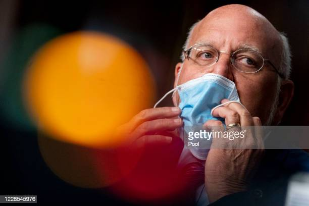 Centers for Disease Control and Prevention Director Dr. Robert Redfield puts his mask on after speaking at a hearing of the Senate Appropriations...
